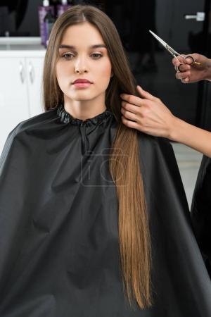 stylist cutting hair of woman