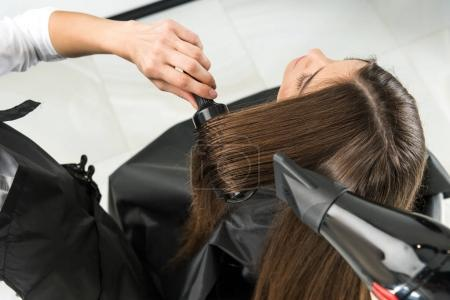 Photo for Top view of hairdresser drying hair of young woman in beauty salon - Royalty Free Image