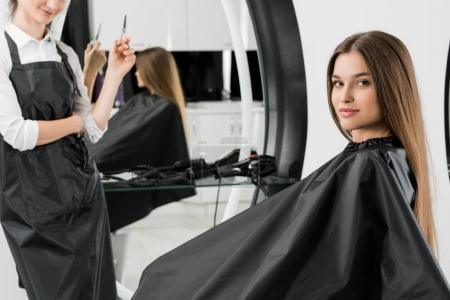 Photo pour Jeune femme avec coiffeur dans un salon de beauté - image libre de droit