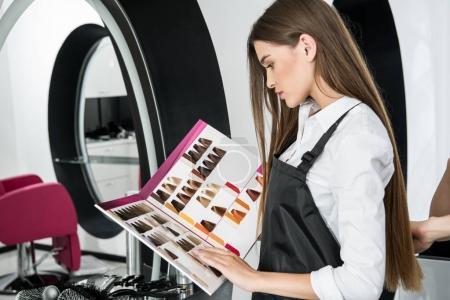 Photo pour Jeune styliste regardant les échantillons de couleur de cheveux catalogue dans le salon de beauté - image libre de droit