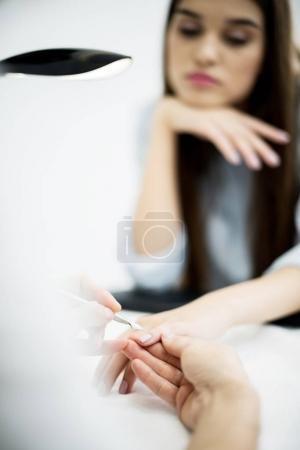 young woman recieving professional manicure