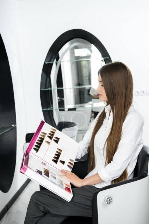 Photo for Young woman looking at hair color samples catalogue in beauty salon - Royalty Free Image