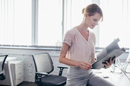 Photo pour Souriant jeune femme d'affaires tenant presse-papiers dans le bureau - image libre de droit
