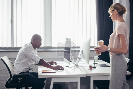 businesswoman bringing coffee to colleague