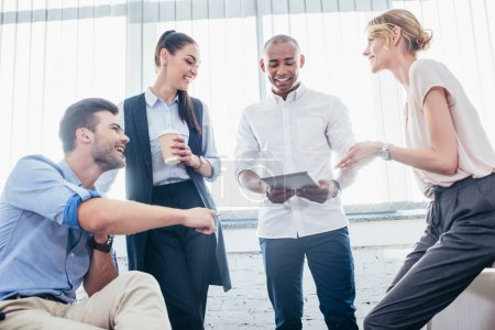 Photo for Smiling young business colleagues using digital tablet in office - Royalty Free Image