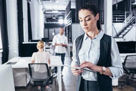 Photo pour Belle jeune femme d'affaires en utilisant une tablette numérique tout en restant au bureau - image libre de droit