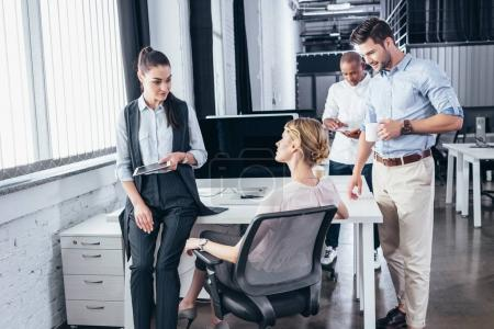 Photo for Young multiethnic business people in office talking in office - Royalty Free Image
