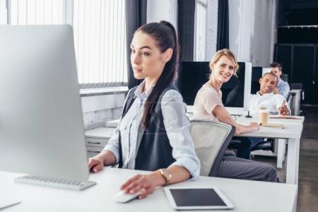 Photo pour Jeune femme d'affaires à l'aide d'ordinateur de bureau tout en souriant collègues assis derrière - image libre de droit