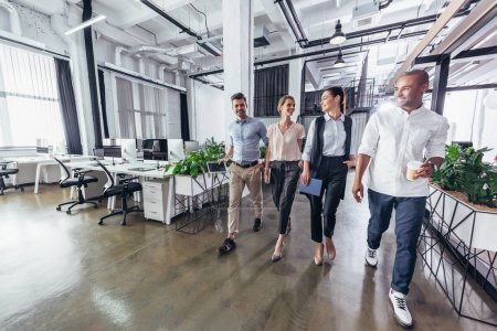 Photo for Smiling young business colleagues talking while walking in office - Royalty Free Image