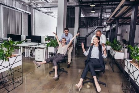 Photo pour Excités jeunes gens d'affaires sur des chaises s'amuser ensemble dans le bureau - image libre de droit