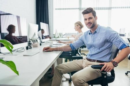 Photo for Handsome young businessman smiling at camera while working in office - Royalty Free Image