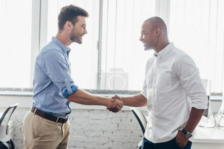 Photo for Young multiethnic businessmen shaking hands and smiling each other - Royalty Free Image