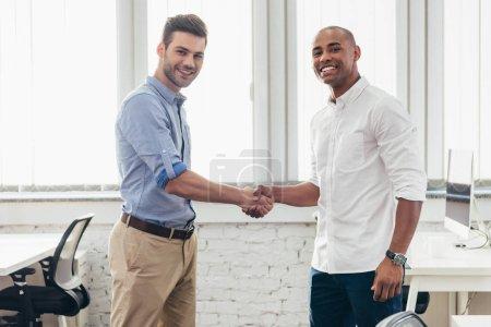 Photo pour Jeunes hommes d'affaires multiethniques serrant la main et souriant à la caméra - image libre de droit