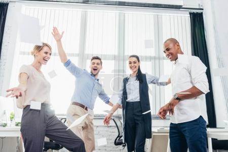 Photo pour Jeunes gens d'affaires joyeux triomphant et jetant des papiers dans le bureau - image libre de droit