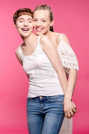 Photo pour Demi-longueur prise de vue de couple lesbienne heureux tenant la main et regardant la caméra - image libre de droit