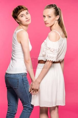 Photo pour Plan à mi-longueur d'un couple de lesbiennes tenant la main et regardant la caméra - image libre de droit