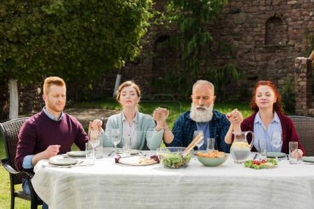 Foto de Cogidos de la mano mientras rezaba durante la cena en el campo de la familia - Imagen libre de derechos