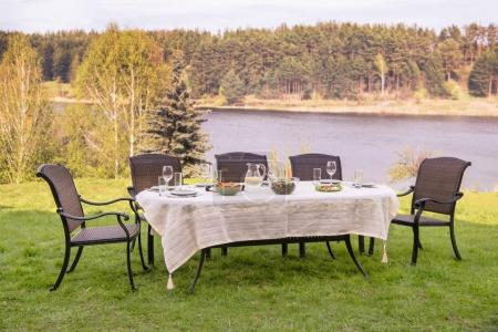Photo for Empty table with dinner and tableware and chairs at riverbank - Royalty Free Image