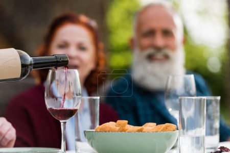 Photo for Selective focus of senior couple looking at pouring red wine into glass process - Royalty Free Image