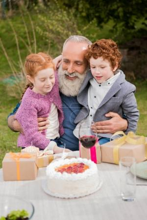 Kids greeting grandfather at birthday celebration