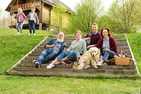 Photo for Family having picnic while kids having fun near by in village - Royalty Free Image
