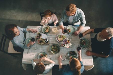Photo pour Vue aérienne de la famille multigénération dînant ensemble à la maison - image libre de droit