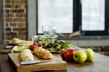 Photo for Selective focus of bread on wooden cutting board and fresh apples on tabletop - Royalty Free Image