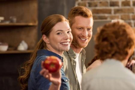 Photo pour Foyer sélectif de la femme souriante montrant pomme fraîche à la main - image libre de droit