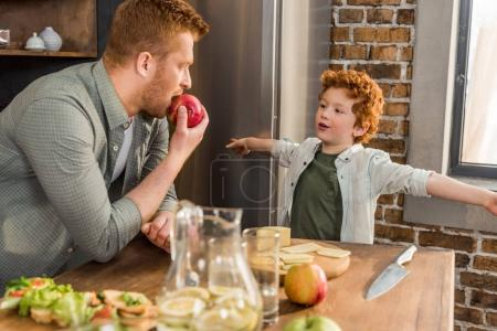 Photo for Little boy looking at father eating fresh apple at home - Royalty Free Image