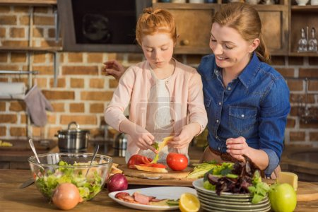 daughter and mother making salad