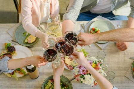 Photo for Partial view of family clinking glasses while having dinner together - Royalty Free Image