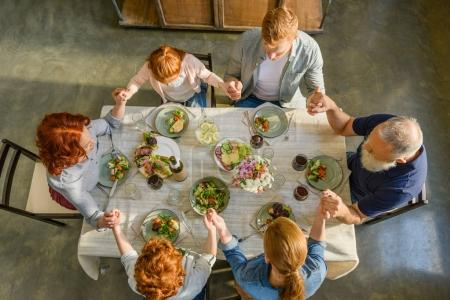 Photo for Overhead view of family holding hands and praying while having dinner together - Royalty Free Image