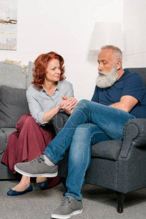 Foto de Senior pareja cogidos de la mano descansando en el sofá en casa - Imagen libre de derechos
