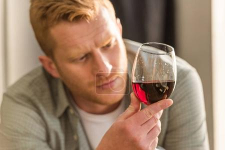 Photo for Selective focus of pensive man looking at glass of wine in hand - Royalty Free Image