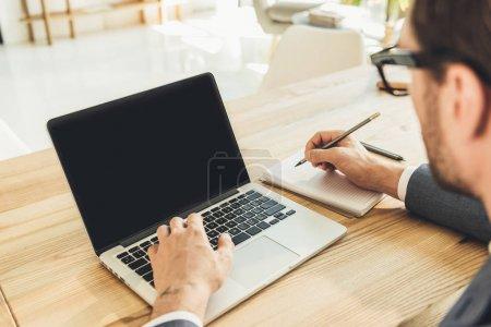 Photo pour Homme d'affaires en costume de travail avec son ordinateur portable et écrire dans un cahier avec un crayon - image libre de droit