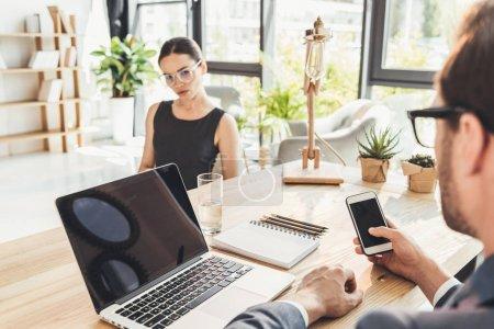 Photo pour Jeune homme d'affaires et son secretery assis au bureau en bureau, discutant des travaux - image libre de droit