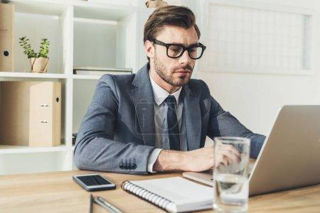 Photo pour Jeune homme d'affaires au bureau assis à son bureau et travaillant sur ordinateur portable - image libre de droit