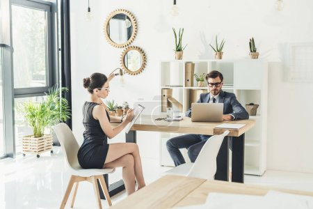 Businessman and secretery working in office