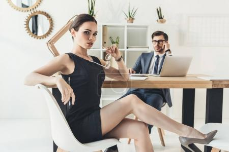 Photo for Young businesswoman sitting seductively on a chair in office with glasses in her hand - Royalty Free Image