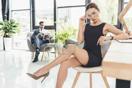 Photo for Young businesswoman in black dress and glasses sitting in a chair at office with legs crossed - Royalty Free Image
