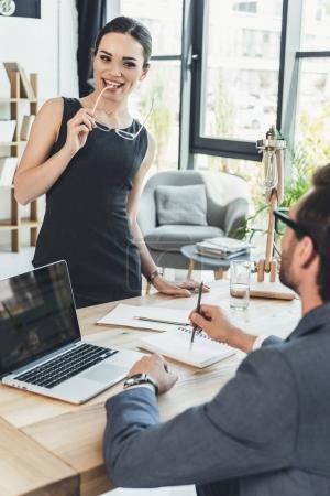 Secretery smiling flirtatiously at boss