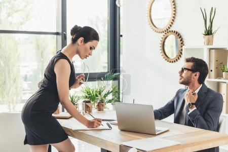 Seductive secretery leaning over desk