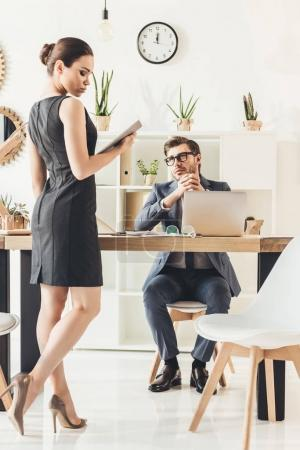 Businessman looking at seductive secretery