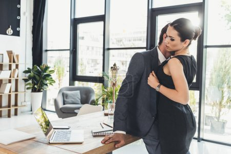 Man kissing woman on neck in office
