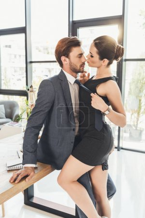 Photo for Young man in a suit sitting on table with beautiful woman pulling him by necktie and leaning in for kiss - Royalty Free Image