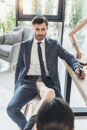 Woman in high heels placing her foot on a chair between legs of young man in business sui