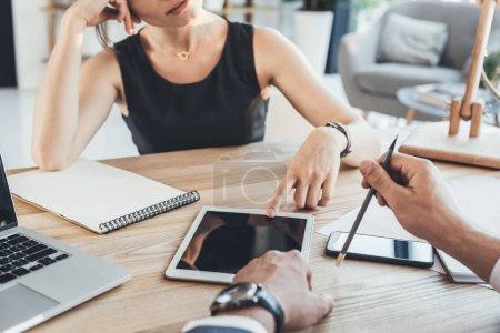 Photo pour Plan recadré de mains masculines tenant un crayon et une femme pointant sur un écran de tablette numérique sur un bureau en bois - image libre de droit