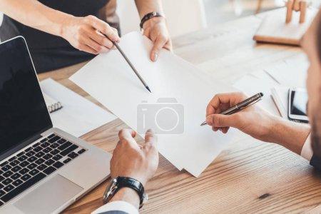 Photo pour Recadrée tir de femme montrant où signer sur la paperasse et mains mâles signature des documents - image libre de droit