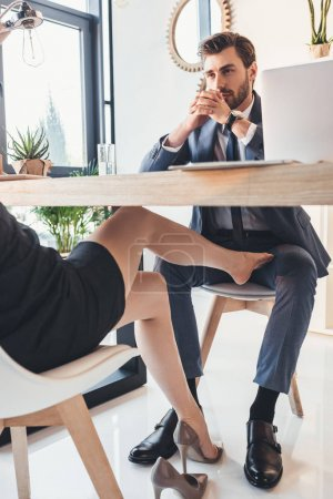 Photo for Young businessman sitting at desk with woman putting her foot between his legs under the table - Royalty Free Image