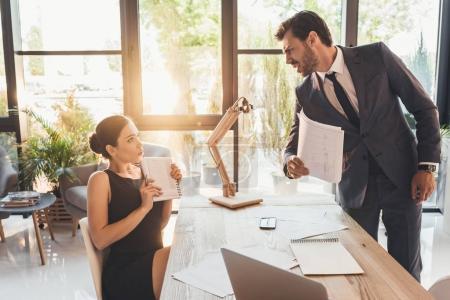 Photo pour Homme d'affaires furieux en combinaison avec de la paperasse dans sa main en criant à son secretery - image libre de droit